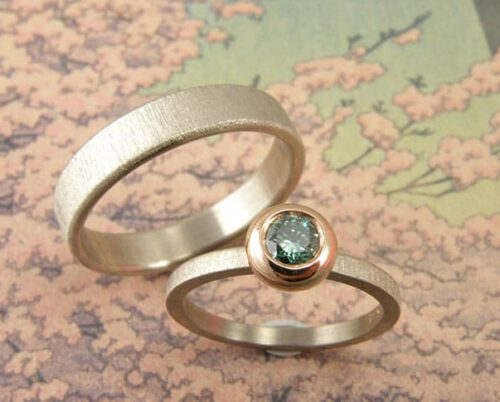 Trouwringen 'Fluweel & Boleet'. Witgouden ring met paraïbagroene diamant in een roodgouden boleet zetting. Witgouden ring. Wedding rings 'Velvet & Boletus'. White golden ring with paraïbagreen diamond. White golden ring. Uit het Oogst Atelier Amsterdam.