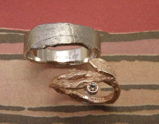Gouden trouwringen 'Boomgaard' en 'Erosie. 'Roodgouden takjes met blaadje en diamant. Witgouden stoere structuur ring. Ontwerp en creatie van Oogst Goudsmeden.