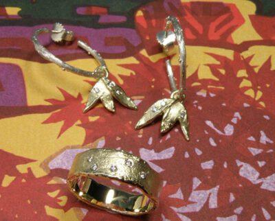 Oorsieraden & ring 'Erosie' van eigen goud vervaardigde blaadjes oorhangers met elk 2 eigen diamanten, los bungelend aan zilveren takjes en van eigen goud vervaardigde structuur ring met 5 eigen diamanten. Earrings & ring 'Erosion' earrings made of heirloom gold and diamonds, loosely hanging on silver twigs and structure ring made of heirloom gold with 5 heirloom diamonds. Oogst goudsmeden Amsterdam.