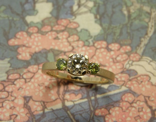 Verlovingsring 'Eenvoud'. Geelgouden ring met een 0,40 crt diamant en 2x 0,08 crt groene diamanten. Engagement ring 'Simplicity'. Yellow golden ring with a 0,40 crt diamond and 2x 0,08 crt diamonds. Uit het Oogst atelier Amsterdam.