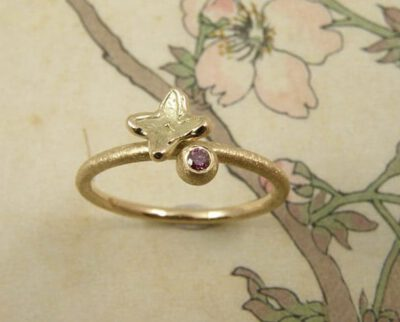 Verlovingsring 'In bloei'. Geelgouden ring met bol, 0,04 crt roze diamant met een bloemetje. Engagement ring 'In bloom'. Yellow golden ring with sphere, 0,04 crt pink diamond and a flower. Oogst goudsmeden Amsterdam.