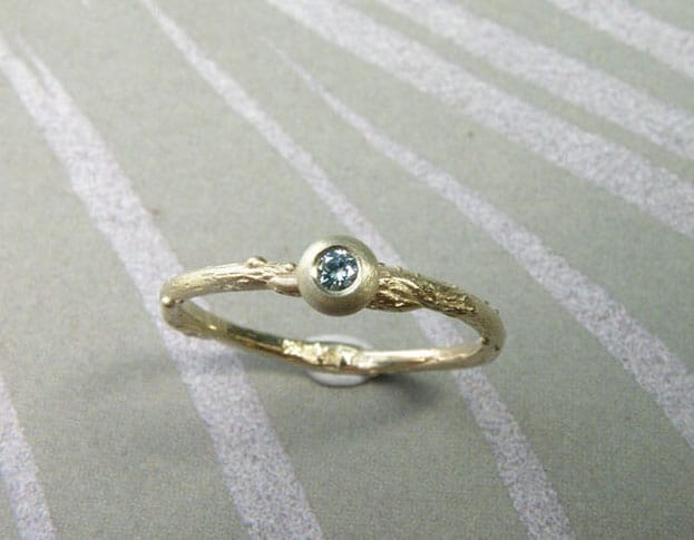 Verlovingsring 'Boomgaard' Geelgouden takjesring met 0,05 crt ijsblauwe diamant. Engagement ring 'Orchard'. Yellow golden twig ring with a 0,05 crt ice blue diamond. Oogst goudsmeden Amsterdam.