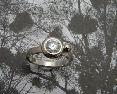Ring 'Boleet' witgouden hamerslag ring met een eigen diamant uit een erfstuk met een speels bolletje ernaast. Ring 'Boletus' white golden ring with hammering, heirloom diamond and a playful sphere. Oogst goudsmeden Amsterdam.