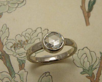 Verlovingsring 'Ritme'. Witgouden ring met kussen hamerslag en 0,85 crt diamant. Engagement ring 'Rhythm'. White golden ring with hammering and 0,85 crt diamond. Oogst goudsmeden Amsterdam.