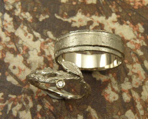 Trouwringen 'Boomgaard' en 'Erosie'. Witgouden ring met takje, blaadje en diamant. Witgouden gelaagde structuur ring. Wedding rings 'Orchard' & 'Erosion'. White golden ring with twig, leaf and diamond. White golden layered ring with structure. Uit het Oogst atelier Amsterdam.