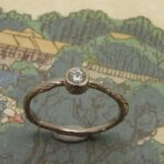 Verlovingsring 'Boomgaard'. Witgouden takje met 0,10 crt diamant. Engagement ring 'Orchard'. White golden twig with 0,10 crt diamond. Oogst goudsmeden Amsterdam.