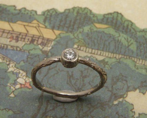 Verlovingsring 'Boomgaard'. Witgouden takje met 0,10 crt diamant. Engagement ring 'Orchard'. White golden twig with 0,10 crt diamond. Oogst goudsmeden Amsterdam.