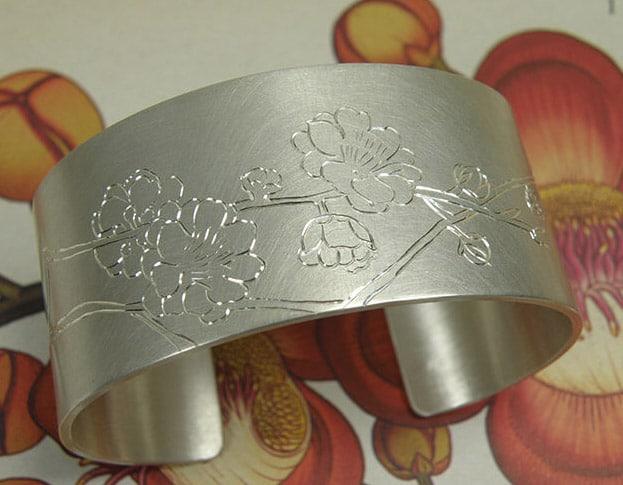 Zilveren klemarmband met Japanse kersenbloesem handgravure. silver cuff with hand engraved Japanese cherry blossom. Uit het Oogst atelier Amsterdam.