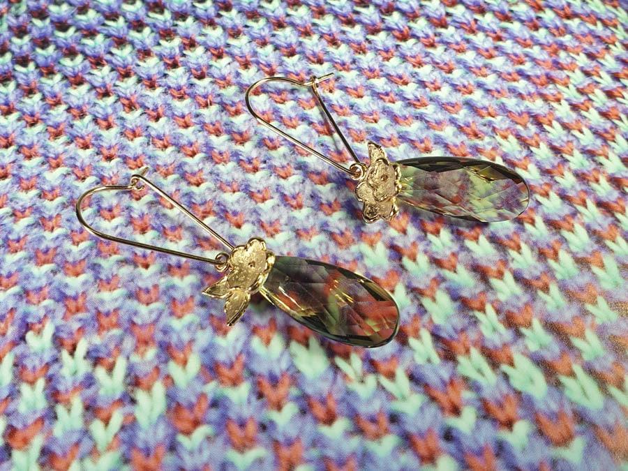 Oorsieraden 'In bloei'. Roodgouden bloemen en briolet geslepen rookkwarts aan lange haakjes. Uit het Oogst goudsmid atelier Amsterdam. Rose gold smokey quartz earrings.