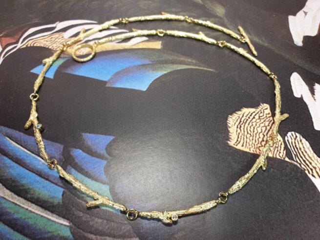 Geelgouden collier 'Boomgaard', verfijnde takjes met blaadjes en sprankelende diamant. Oogst goudsmid Amsterdam atelier. Handgemaakte sieraden Colliers