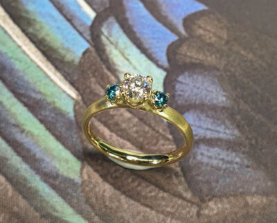 Verlovingsring Eenvoud geelgoud met diamant en blauwe diamant. Engagement ring Simplicity with diamond and 2 blue diamonds. Oogst goudsmid Amsterdam.
