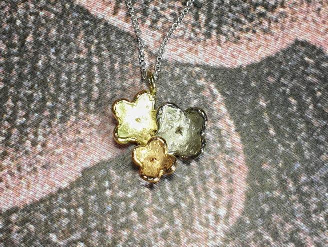 In bloei hanger 3 bloemen in geelgoud, witgoud en roodgoud. Baargoud. Geboortecadeau. Birth present. Gold pendant Flowers in yellow gold, white gold and rose gold. Oogst edelsmid Amsterdam
