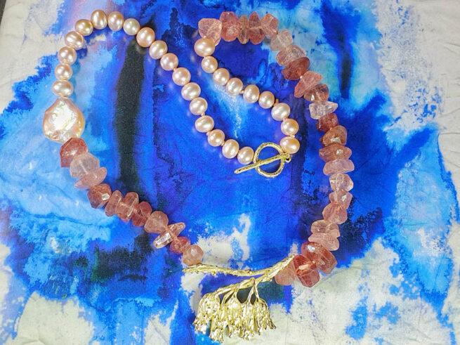 Collier 'In bloei' geelgouden bloesem, strawberry quartz en roze zoetwaterparels. Oogst goudsmid Amsterdam.