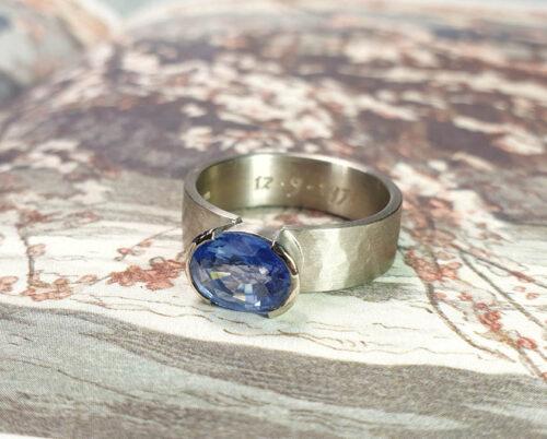 Witgouden ring Ritme met hamerslag en met eigen saffier. Maatwerk cadeau uit het Oogst goudsmid atelier Amsterdam. White gold mens ring hammered with sapphire.