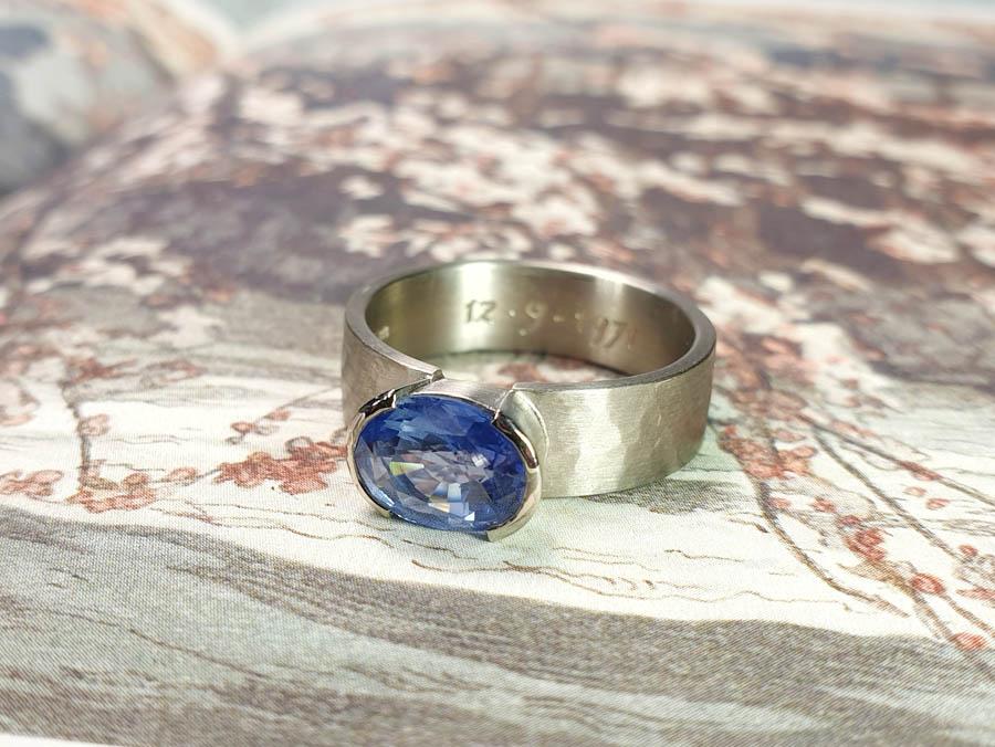 Witgouden ring vervaardigd van witgoud met hamerslag en met eigen saffier. Maatwerk cadeau uit het Oogst goudsmid atelier Amsterdam. White goold mens ring hammered with sapphire.
