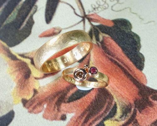 Trouwringen Ritme Boleet. Geelgouden ring met roze diamant en besje. Geelgouden ring met hamerslag. Wedding rings Rhythm and Boletus. Yellow gold hammered rings with pink diamonds. Huwelijksringen Oogst goudsmid Amsterdam.