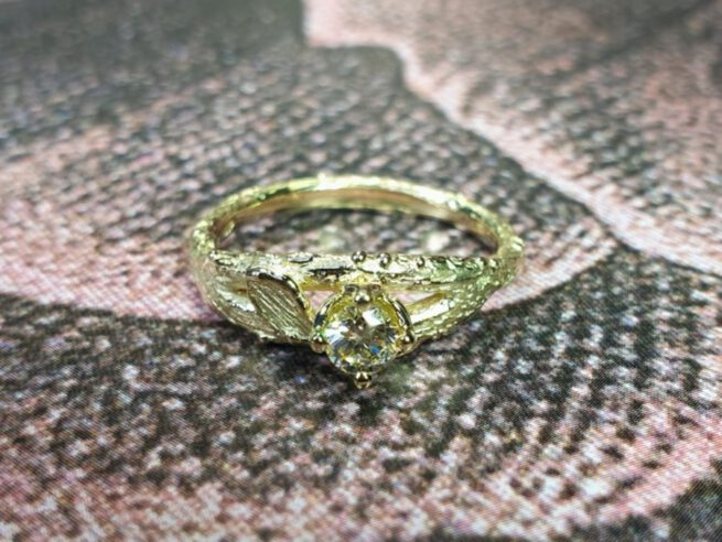 Verlovingsring geelgouden takje met diamant cape in chaton. Boomgaard. Engagement ring yellow gold twig with diamond cape. orchard. Design by Oogst Goudsmid Amsterdam