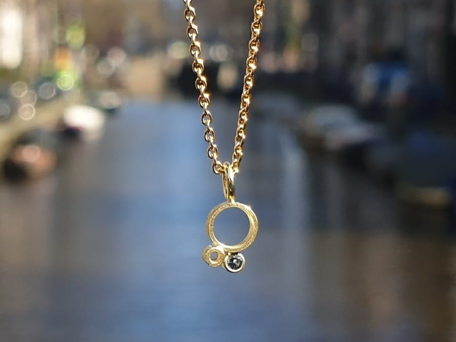 Geelgouden hanger 'Lichtpuntje' met blauwe spinel. Yellow gold pendant 'Ray of light' with a blue spinel. Oogst goudsmid Amsterdam