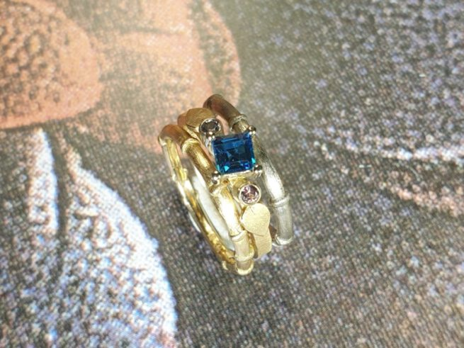 Rosé gold ring 'Cluster' with blue topaz and pink spinel and leaves. Stack rings 'Bamboo'. Oogst goldsmith Amsterdam