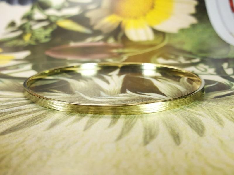 Geelgouden rinkelarmband 'Ritme'met spitse hamerslag. White gold bracelet 'Rhythm' with hammering. Design & creation by Oogst Amsterdam. Goldsmith Goudsmid