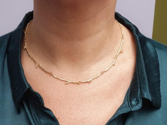 Geelgouden collier 'Boomgaard', verfijnde takjes met blaadjes en sprankelende diamant. Oogst goudsmid Amsterdam atelier.