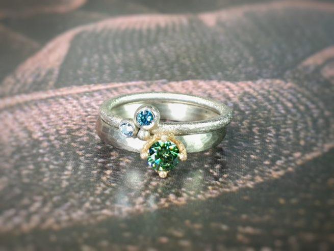 Witgouden 'Ritme' ring met groene diamant. Witgouden 'Bessen' ring met blauwe diamanten. Oogst edelsmid Amsterdam