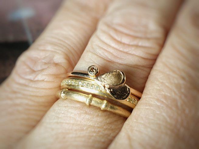 Aanschuifringen. Geelgouden 'Bamboe' ring, roségouden 'Eenvoud' ring met rondom diamanten en roodgouden 'Besje' ring met blaadjes en bruine diamant. Oogst goudsmid Amsterdam