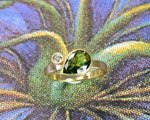 Geelgouden ring Verzameling met groene peervormige toermalijn en een diamant. Yellow gold ring 'Cluster' with a pear shaped green tourmaline and a diamond. Push present. Geboortecadeau. oogst goudsmid Amsterdam