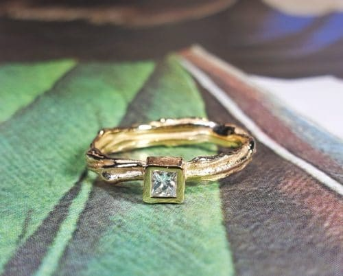 Roségouden trouwring 'Twist' met princess geslepen diamant. Ontwerp van Oogst goudsmeden Amsterdam Geelgouden 'Zwammen' armband met handgravure en toermalijn kristal. Ontwerp van Oogst goudsmid in Amsterdam uit de Amorf vs Kristallijn collectie.