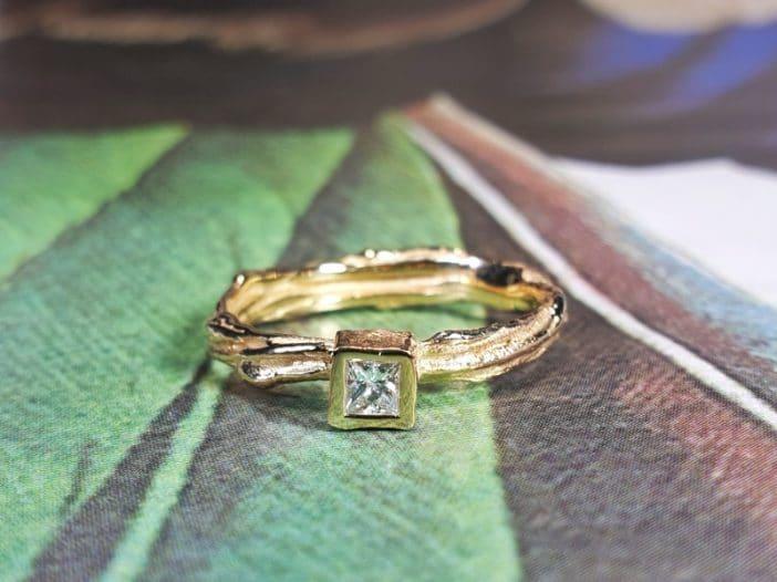 Roségouden verlovingsring 'Twist' met princess geslepen diamant. Ontwerp van Oogst goudsmeden Amsterdam Ontwerp van Oogst goudsmid in Amsterdam uit de Amorf vs Kristallijn collectie.