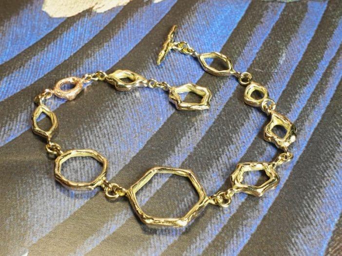Geelgouden armband 'Amorf Hoekig' met een roodgouden schakel. Ontwerp van Oogst goudsmid in Amsterdam uit de Amorf vs Kristallijn collectie.