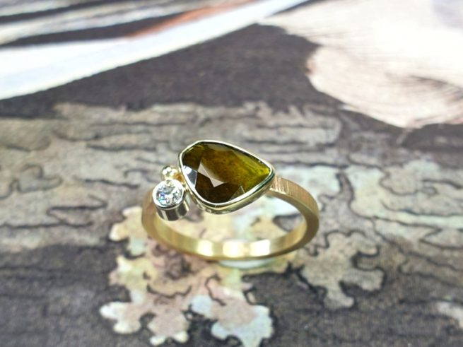 Geelgouden 'Verzameling' verlovingsring met groene toermalijn en diamant. Uit het goudsmid atelier van Oogst in Amsterdam
