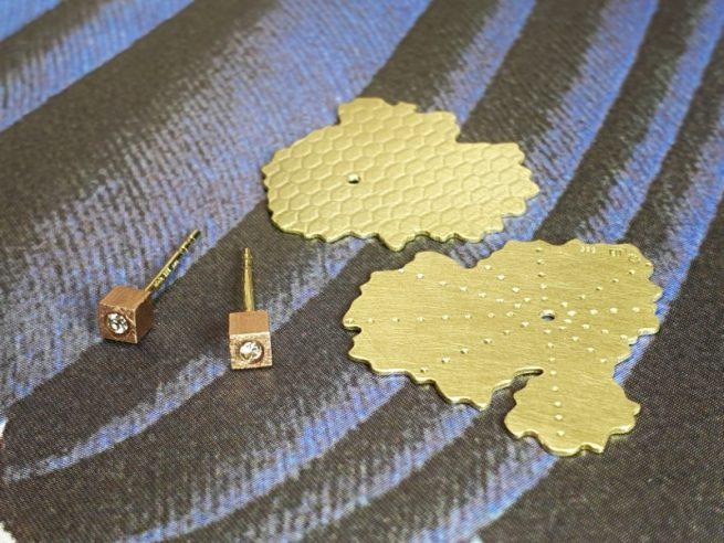 Geelgouden 'Zwam' oorsieraden met roodgouden kubusjes met diamant. Ontwerp Oogst goudsmid Amsterdam Geelgouden 'Zwammen' armband met handgravure en toermalijn kristal. Ontwerp van Oogst goudsmid in Amsterdam uit de Amorf vs Kristallijn collectie.