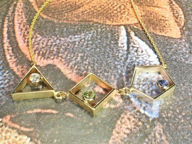 Geboortesieraad. Collier 'Verzameling in geelgoud met diamant, spinel en saffier, de geboortestenen van haar kinderen. Goudsmid Oogst in Amsterdam