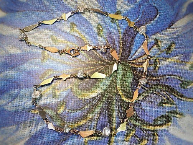 Collier 'Vouwen' in roodgoud, geelgoud, witgoud en roségoud met grijze keshi parels. Ontwerp van Oogst goudsmid in Amsterdam uit de Amorf vs Kristallijn collectie.