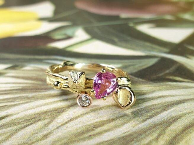 Blog over Saffier. Geelgouden 'Twist' ring met een roségouden perzik, een kristal en 0,65 crt peergeslepen roze korund en 0,11 crt diamant brown . Ontwerp van Oogst goudsmid in Amsterdam voor de Amorf vs Kristallijn collectie.