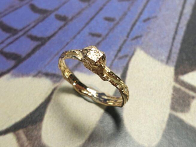 Geelgouden ring 'Twist & Kristal'. Ontwerp uit de Amorf vs Kristallijn collectie van goudsmid Oogst in Amsterdam