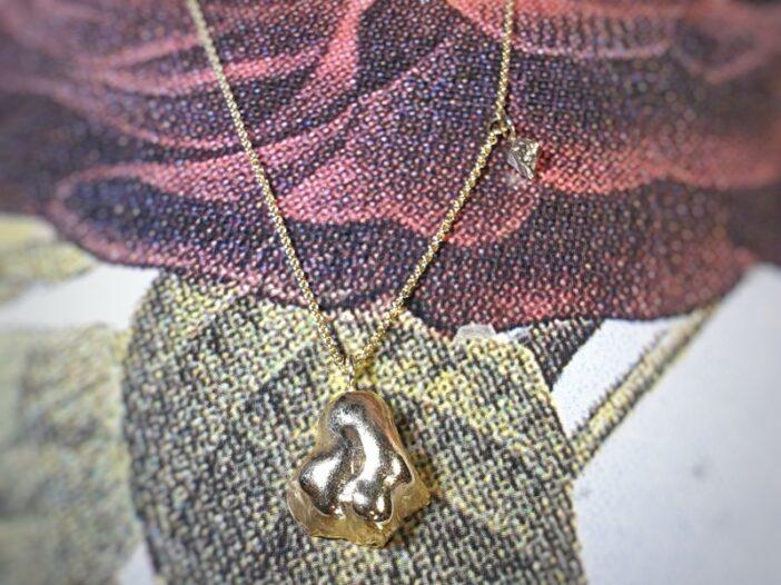 Geelgouden collier 'Wolk & Kristal' met geelgouden wolk en witgouden kristalletje. Ontwerp uit de Amorf vs Kristallijn collectie van goudsmid Oogst in Amsterdam