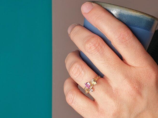 Geelgouden 'Twist' ring met een roségouden perzik, een kristal en 0,65 crt peergeslepen roze korund en 0,11 crt diamant brown . Ontwerp van Oogst goudsmid in Amsterdam voor de Amorf vs Kristallijn collectie.