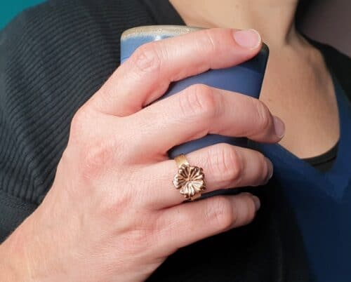 Geelgouden ring 'In bloei'met roodgouden bloemmotief. Ontwerp van Oogst goudsmid in Amsterdam.