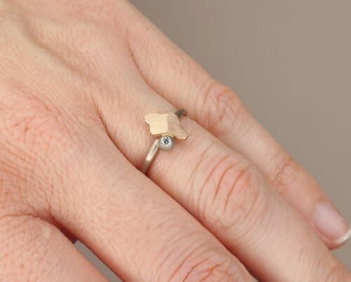 Witgouden ring 'Vouwen' met roodgouden element en bes met 0,03 ct diamant. Ontwerp van Oogst goudsmid in Amsterdam uit de Amorf vs Kristallijn collectie.