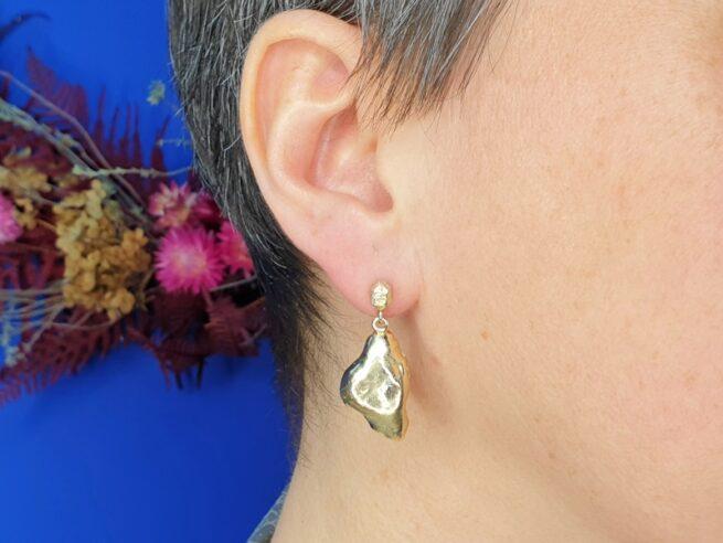 Geelgouden oorsieraden 'Wolken' met een hoekig kristal en steker. Ontwerp van Oogst goudsmid Amsterdam uit de Amorf vs Kristallijn collectie.