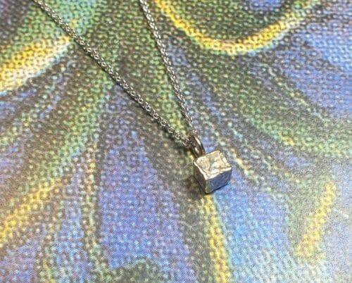 Witgouden collier met witgouden kubus kristalletje hanger. Ontwerp uit de Amorf vs Kristallijn collectie van goudsmid Oogst in Amsterdam
