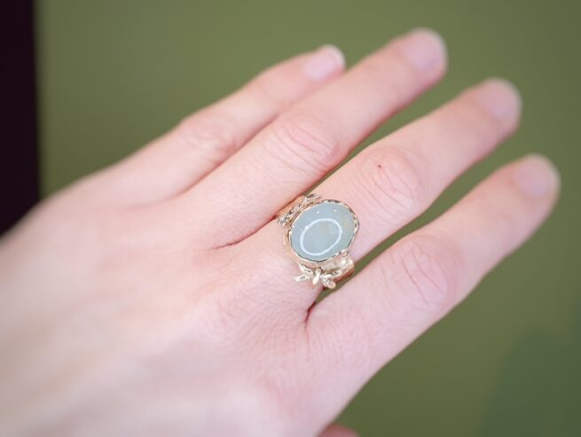 Yellow gold ring with a cabochon cut Aquamarine and dragonflies, one in white gold. Designed and created by Oogst goldsmith in Amsterdam.