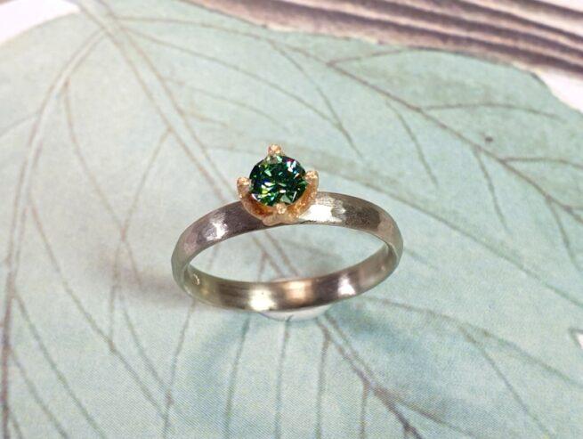 Witgouden 'Ritme'ring met hamerslag en groene diamant in een roodgouden tulpchaton.