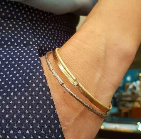 Witgouden 'Boomgaard' rinkelband. Roodgouden 'ritme' armband en geelgouden 'bessen' armband samen gedragen.. Uit het Oogst atelier Amsterdam.