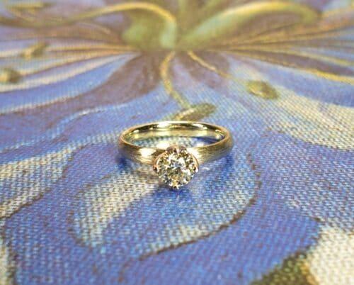 Geelgouden 'Ritme' verlovingsring met 0,52 ct cape diamant en spitse hamerslag. Ontwerp van Oogst Goudsmeden.