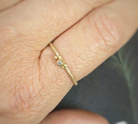 Geelgouden ring 'Besjes' met een diamantje om de vinger. Sieraadontwerp Oogst in Amsterdam.