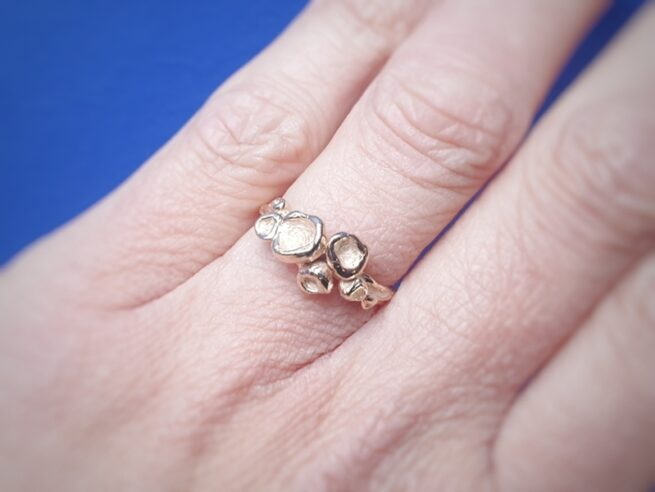 Rosé gold organic ring 'Peaches' shown on the hand. Jewellery design by Oogst in Amsterdam