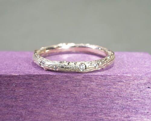Geelgouden verlovingsring met diamanten rondom speels verdeeld gezet. Ontwerp van Oogst Sieraden in Amsterdam